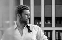Το όμορφο hunky άτομο με το ξεκουμπωμένο πουκάμισο και το χαλαρό bowtie στέκεται στο μπαλκόνι ξενοδοχείων με το σκηνικό sckyscrap Στοκ Φωτογραφίες