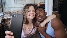 Το όμορφο multiethnic ζεύγος παίρνει τη φωτογραφία selfie στο smartphone Η λαβή γυναικών το smartphone, άνδρας την φιλά και γελά φιλμ μικρού μήκους