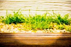 Το ύφος φύσης υποβάθρου κατάλληλο για εισάγει την εικόνα κειμένων και προϊόντων Με την πράσινη χλόη και το καφετί ξύλινο πρώτο πλ Στοκ φωτογραφία με δικαίωμα ελεύθερης χρήσης