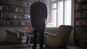 Το ώριμο άτομο περπατά στο δωμάτιο που εφοδιάζεται με τον παλαιό καναπέ, armhairs, πίνακας, ράφια απόθεμα βίντεο