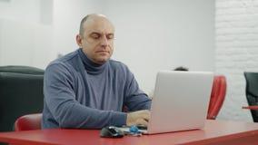 Το ώριμο άτομο προγραμματιστών εργάζεται στο lap-top στο γραφείο απόθεμα βίντεο
