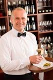 το ώριμο εστιατόριο γυαλιού ράβδων εξυπηρετεί το κρασί σερβιτόρων στοκ φωτογραφία με δικαίωμα ελεύθερης χρήσης