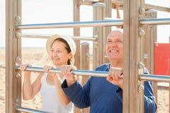 Το ώριμο ζεύγος που εκπαιδεύει μαζί επάνω σηκώνει το φραγμό Στοκ φωτογραφία με δικαίωμα ελεύθερης χρήσης