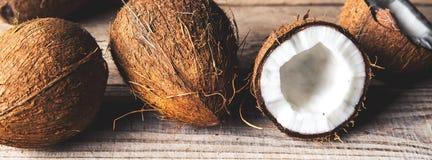 Το ώριμο μισό έκοψε την καρύδα σε ένα ξύλινο υπόβαθρο Το ώριμο μισό έκοψε την καρύδα σε ένα ξύλινο υπόβαθρο Κρέμα και έλαιο καρύδ Στοκ εικόνα με δικαίωμα ελεύθερης χρήσης