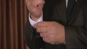 Το ώριμο χέρι ατόμων στερεώνει ένα κουμπί στο μανίκι του πουκάμισου απόθεμα βίντεο