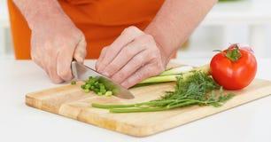 Το ώριμο χέρι ατόμων ` s με ένα μαχαίρι έκοψε το πράσινο κρεμμύδι στο α ο πίνακας Στοκ Εικόνες