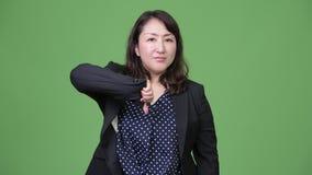 Το ώριμο όμορφο ασιατικό δόσιμο επιχειρηματιών φυλλομετρεί κάτω απόθεμα βίντεο