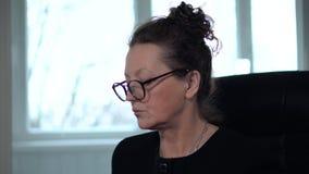 Το ώριμο brunette γυναικών στα γυαλιά και τη μαύρη δακτυλογράφηση κοστουμιών στον υπολογιστή κοιτάζει στο όργανο ελέγχου και στο  απόθεμα βίντεο