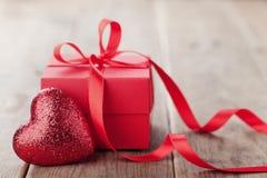 Το δώρο ή το παρόν κιβώτιο με την κόκκινη κορδέλλα τόξων και ακτινοβολεί καρδιά στον ξύλινο πίνακα για την ημέρα βαλεντίνων Στοκ Εικόνες