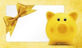 Το δώρο καρτών με τη piggy τράπεζα, χρυσό τόξο κορδελλών, απομόνωσε σε κίτρινο Στοκ φωτογραφία με δικαίωμα ελεύθερης χρήσης