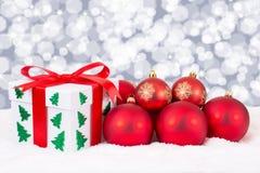 Το δώρο καρτών Χριστουγέννων ανάβει τα δώρα διακοσμήσεων και τις κόκκινες σφαίρες Στοκ Εικόνες