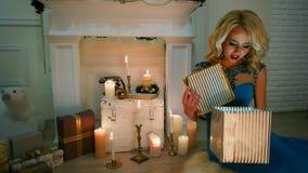 Το δώρο του νέου έτους, έκπληξη, ευτυχής συνεδρίαση κοριτσιών από την εστία με τα κεριά ανοίγει τα δώρα για τα Χριστούγεννα, ανοί απόθεμα βίντεο