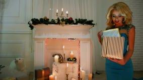 Το δώρο του νέου έτους, έκπληξη, κορίτσι ανοίγει το ωραία τυλιγμένο δώρο, Χαρούμενα Χριστούγεννα Χριστουγέννων σε μια άνετη ατμόσ απόθεμα βίντεο