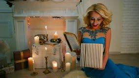 Το δώρο Χριστουγέννων, έκπληξη, το κορίτσι ανοίγει το εσωτερικό δώρων είναι ελαφριά, ευτυχής συνεδρίαση κοριτσιών από την εστία μ απόθεμα βίντεο
