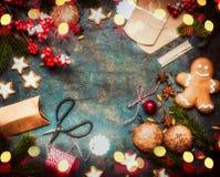 Το δώρο Χριστουγέννων και παρουσιάζει το τύλιγμα με τα μπισκότα διακοπών και τα χειροποίητα κιβώτια εγγράφου στο σκοτεινό εκλεκτή Στοκ Φωτογραφίες