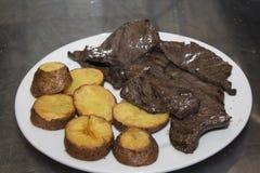 Το Anticuchos, περουβιανή κουζίνα, έψησε το σουβλισμένο κρέας καρδιών βόειου κρέατος με το βρασμένο τσίλι σάλτσας πατατών στη σχά Στοκ εικόνα με δικαίωμα ελεύθερης χρήσης