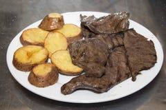 Το Anticuchos, περουβιανή κουζίνα, έψησε το σουβλισμένο κρέας καρδιών βόειου κρέατος με το βρασμένο τσίλι σάλτσας πατατών στη σχά Στοκ Εικόνες