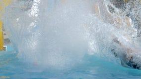 Το Aquapark, εύθυμα κορίτσια φίλων που γλιστρούν στο νερό γλιστρά και βουτά σε Poolside με το ράντισμα στις διακοπές απόθεμα βίντεο