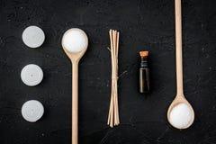 Το Aromatherapy για χαλαρώνει την έννοια Άλας, κεριά και έλαιο SPA στη μαύρη τοπ άποψη υποβάθρου Στοκ Φωτογραφίες