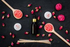 Το Aromatherapy για χαλαρώνει την έννοια Αυξήθηκε οφθαλμοί, άλας SPA, κεριά και έλαιο στη μαύρη τοπ άποψη υποβάθρου Στοκ Εικόνες