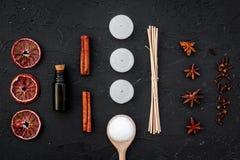 Το Aromatherapy για χαλαρώνει την έννοια Η SPA αλατίζει, κεριά και πετρέλαιο με την κανέλα καρυκευμάτων στη μαύρη τοπ άποψη υποβά Στοκ Εικόνες