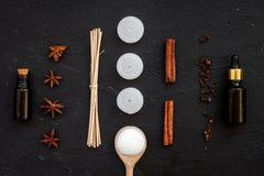 Το Aromatherapy για χαλαρώνει την έννοια Η SPA αλατίζει, κεριά και πετρέλαιο με την κανέλα καρυκευμάτων στη μαύρη τοπ άποψη υποβά Στοκ Φωτογραφίες