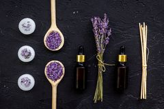 Το Aromatherapy για χαλαρώνει την έννοια Lavender κλάδος, άλας SPA, έλαιο και κεριά στη μαύρη τοπ άποψη υποβάθρου Στοκ Φωτογραφίες