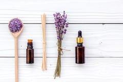 Το Aromatherapy για χαλαρώνει την έννοια Lavender κλάδος, άλας SPA και έλαιο στην άσπρη ξύλινη τοπ άποψη υποβάθρου Στοκ Φωτογραφίες