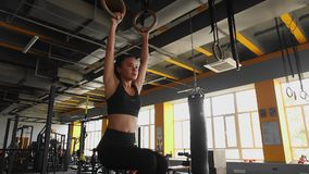 Το Atletic που η νέα ασιατική γυναίκα κάνει τα πόδια τράβηγμα-UPS στα γυμναστικά δαχτυλίδια στη γυμναστική, ασκεί για τα ABS Αθλη απόθεμα βίντεο