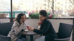 Το Attrcative ανάμιξε τη συνεδρίαση γυναικών φυλών στον πίνακα στο ομιλούν τηλέφωνο κυττάρων καφέδων οδών το σερφ φίλων της απόθεμα βίντεο