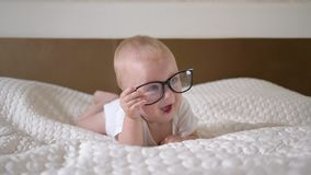 Το Babyhood, πορτρέτο χαριτωμένου λίγο αγόρι παιδιών με τα μεγάλα μπλε μάτια στα γυαλιά βρίσκεται στενό σε επάνω κρεβατιών απόθεμα βίντεο
