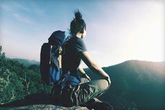 Το Backpacker κάθεται στην άκρη απότομων βράχων απολαμβάνει τη θέα Στοκ Εικόνες