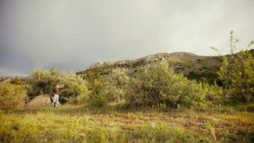 Το Backpacker παίρνει από μια σκηνή στα πλαίσια των όμορφων βουνών απόθεμα βίντεο