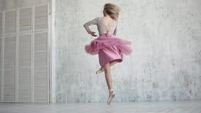 Το Ballerina περιστρέφει στο toe της σε ένα ρόδινο φόρεμα το νέο κορίτσι χορεύει κλασσικό μπαλέτο κίνηση αργή απόθεμα βίντεο