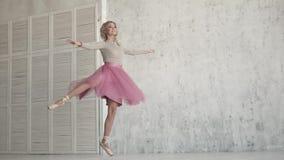 Το Ballerina περιστρέφει στο toe της σε ένα ρόδινο φόρεμα το νέο κορίτσι χορεύει κλασσικό μπαλέτο φιλμ μικρού μήκους