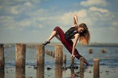 Το Ballerina στο κόκκινο φόρεμα χορεύει στο νερό στο υπόβαθρο θάλασσας Στοκ φωτογραφίες με δικαίωμα ελεύθερης χρήσης