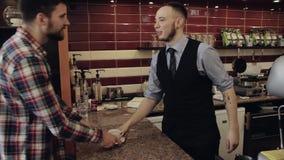 Το Barista δίνει το φλυτζάνι του ζεστού ποτού στο φραγμό Νεαρός άνδρας απόθεμα βίντεο