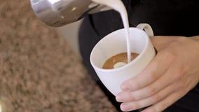 Το Barista ανακατώνει το γάλα και παραγωγή του cappuccino απόθεμα βίντεο