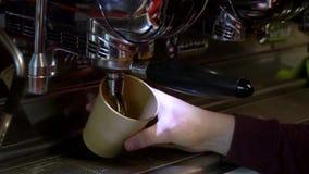 Το Barista κάνει τον καφέ Ο νέος μπάρμαν παρασκευάζει τον καφέ στη μηχανή καφέ κίνηση αργή Ο καφές χύνει σε ένα φλυτζάνι εγγράφου απόθεμα βίντεο