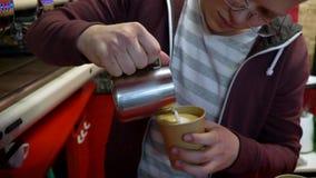 Το Barista κάνει τον καφέ Ο νέος μπάρμαν παρασκευάζει τον καφέ στη μηχανή καφέ κίνηση αργή Το Barista χύνει το γάλα σε ένα φλυτζά απόθεμα βίντεο