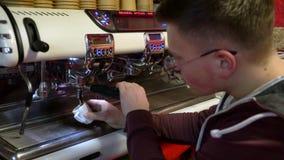 Το Barista κάνει τον καφέ Ο νέος μπάρμαν παρασκευάζει τον καφέ στη μηχανή καφέ Ο καφές χύνει σε ένα άσπρο φλυτζάνι απόθεμα βίντεο