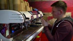 Το Barista κάνει τον καφέ Ο νέος μπάρμαν παρασκευάζει τον καφέ στη μηχανή καφέ o Ο καφές χύνει σε ένα φλυτζάνι εγγράφου απόθεμα βίντεο
