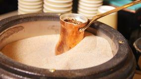 Το barista κινηματογραφήσεων σε πρώτο πλάνο προετοιμάζει τον παραδοσιακό καφέ στην καυτή άμμο απόθεμα βίντεο