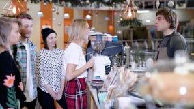 Το Barista συμβουλεύεται τους επισκέπτες του καφέ, οι άνθρωποι στέκονται μπροστά από το μετρητή, το άκουσμα και το χαμόγελο φραγμ απόθεμα βίντεο