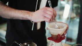 Το Barista χύνει το ζεστό νερό στο φίλτρο με τον καφέ, ανακάτωμα Προετοιμάζεται χύνει, Chemex φιλμ μικρού μήκους