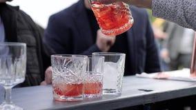 Το Barkeeper προετοιμάζει το ποτό, δίνει bartender χύνει το κοκτέιλ στα ποτήρια με τον πάγο, ο μπάρμαν χύνει booze από τη μίξη το φιλμ μικρού μήκους