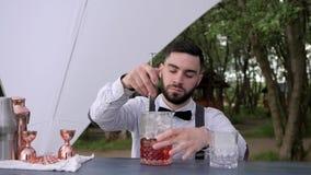 Το Barkeeper στο αντίθετο οινόπνευμα ανακατώματος φραγμών με τον πάγο στο ποτήρι, μπάρμαν κάνει το οινοπνευματώδες ποτό υπαίθρια, απόθεμα βίντεο