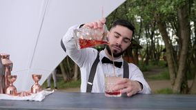 Το Barkeeper χύνει το κατεψυγμένο ποτό στο ποτήρι με τον πάγο, bartender προετοιμάζει το δροσίζοντας κοκτέιλ στο μετρητή φραγμών, απόθεμα βίντεο