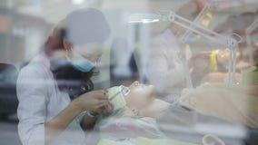 Το Beautician αυξάνεται eyelashes για το όμορφο κορίτσι Διαδικασία επέκτασης Eyelash πυροβολισμός μέσω των παραθύρων απόθεμα βίντεο