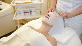 Το Beautician αφαιρεί μια μάσκα αργίλου από το πρόσωπο ενός νέου κοριτσιού στο σαλόνι SPA φιλμ μικρού μήκους